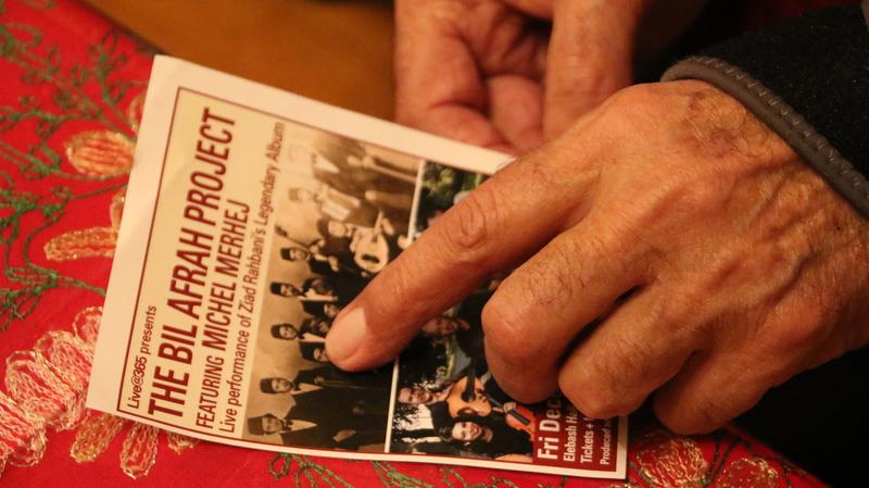 ميشيل مرهج بقلوق يشير لصورته على غلاف ألبوم بالأفراح في منزله في نيويورك في شهر ديسمبر 2018.